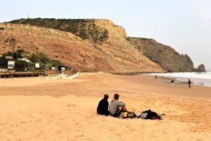 Strand von Praia da Luz bei Lagos mit schwarzem Felsen