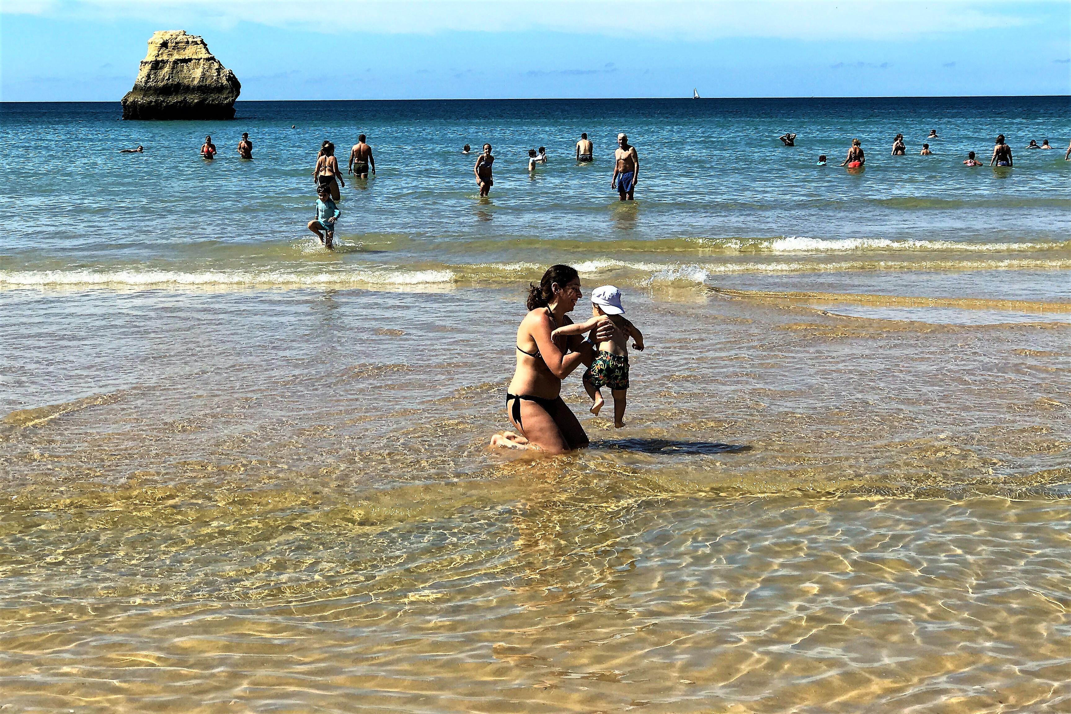 Kleinkind mit Hütchen auf spielt mit Mutter in der Brandung des Atlantiks an der Algarve
